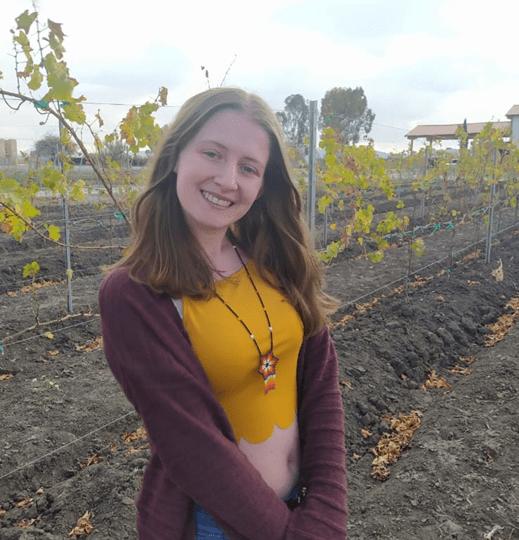 Profile of volunteer Cara, woman wearing yellow crop top smiling.