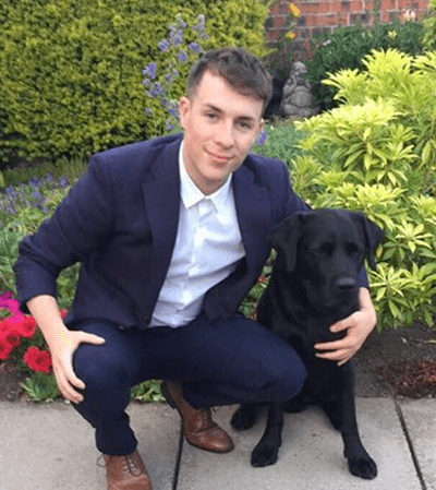 Profile of volunteer Jordan crouched next to black dog.
